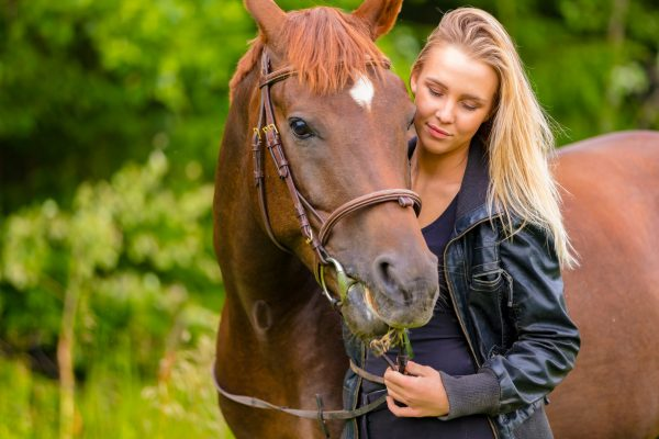 Beautiful young woman with her adult arabian horse standing in a field. Relationship between human and animal.